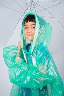 Petit garçon portant un manteau de pluie sur un mur blanc