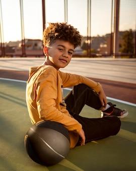 Petit garçon posant avec un ballon de basket