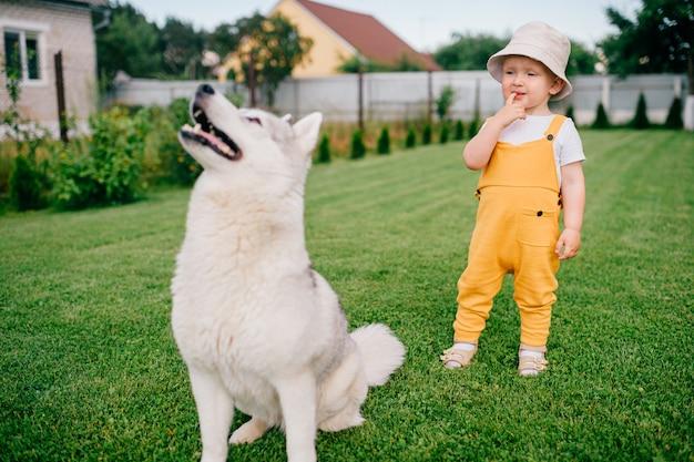 Un petit garçon posant avec le chien dans le jardin