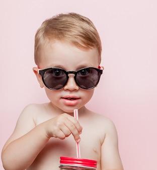 Petit garçon avec pot de limonade fraîche avec un morceau de pastèque et de glace sur le mur rose.