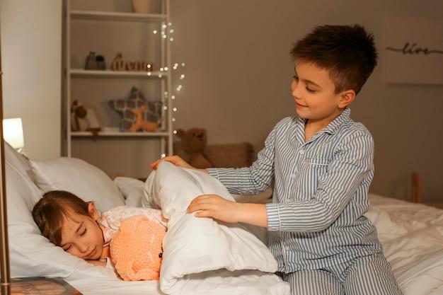 Petit garçon prenant soin de sa sœur dans la chambre la nuit