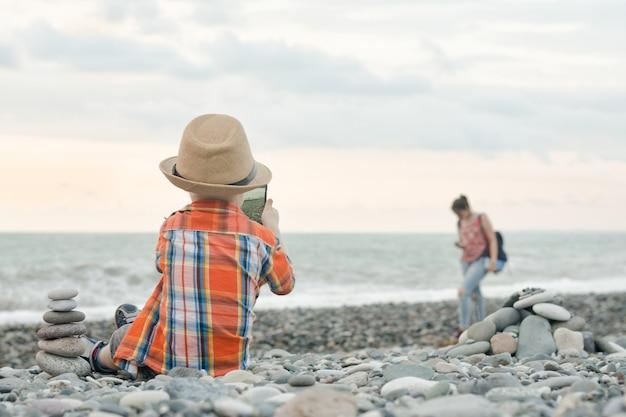 Petit garçon prend des photos sur le téléphone intelligent. assis sur une plage de galets