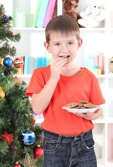 Le petit garçon près de l'arbre de noël mange des biscuits