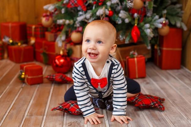 Petit garçon près de sapin de noël avec des coffrets cadeaux