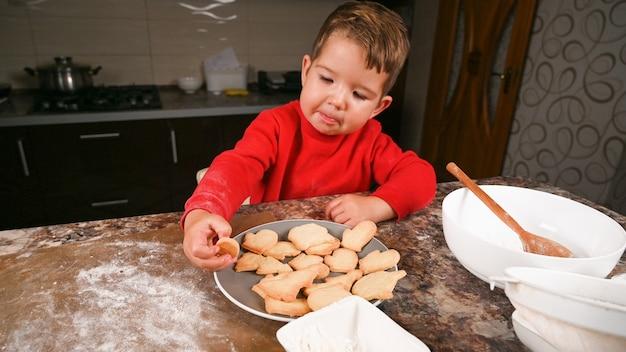 Petit garçon en pull rouge tenant une assiette de biscuits de noël