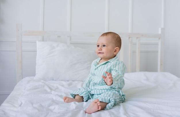 Petit garçon en pyjama est assis sur la literie blanche sur le lit et regarde au loin