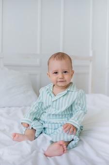 Petit garçon en pyjama rayé est assis sur la literie en coton sur le lit et regarde la caméra