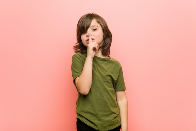 Petit garçon qui garde un secret ou demande le silence.