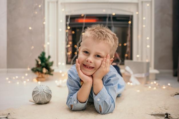 Un petit garçon de race blanche dans une chemise bleue avec un nœud papillon se trouve sur un tapis de fourrure près de la cheminée du nouvel an