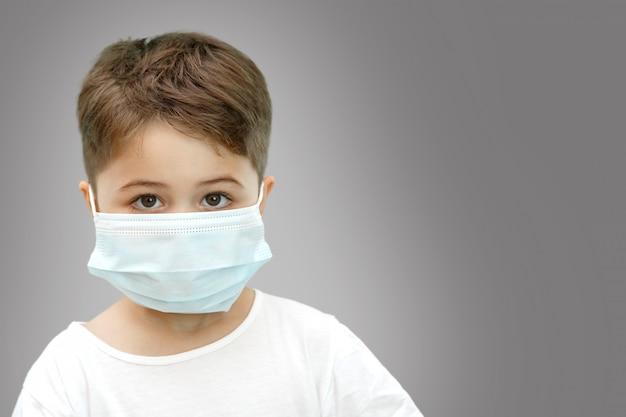 Petit garçon de race blanche dans un masque médical sur fond isolé