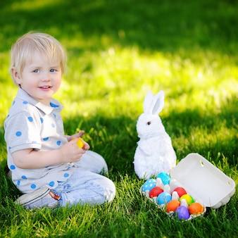 Petit garçon à la recherche de l'oeuf de pâques dans le jardin de printemps le jour de pâques. adorable petit enfant avec un lapin traditionnel