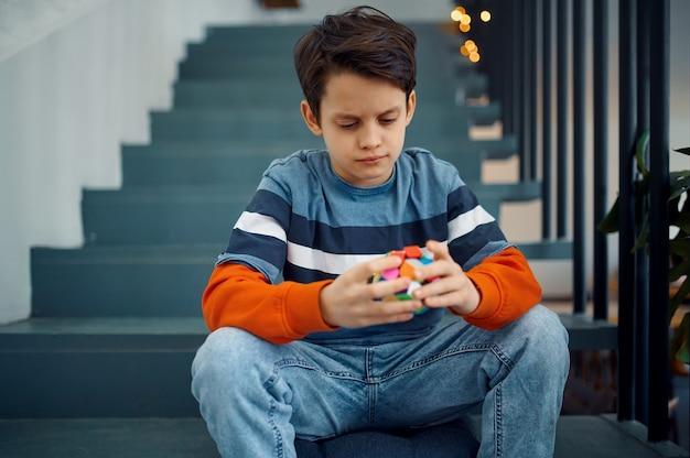 Un petit garçon réfléchi joue avec des cubes de puzzle. jouet pour l'entraînement du cerveau et de l'esprit logique, jeu créatif, résolution de problèmes complexes