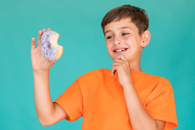 Petit garçon regardant un beignet