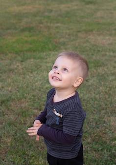 Petit garçon regardant dans le ciel à l'extérieur
