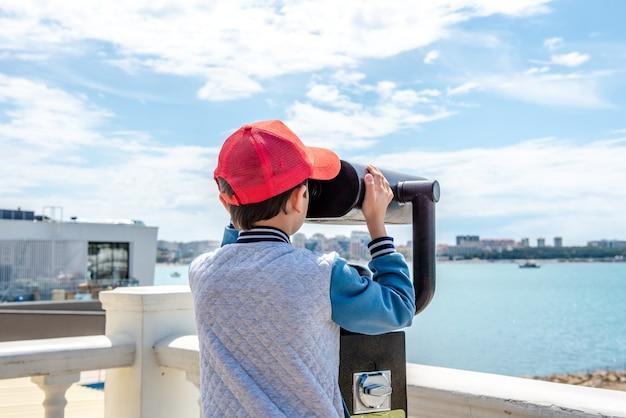Petit garçon regardant dans l'oculaire du télescope touristique voyage destination touristique grossissement paysage