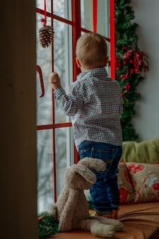 Petit garçon regardant par la fenêtre à noël