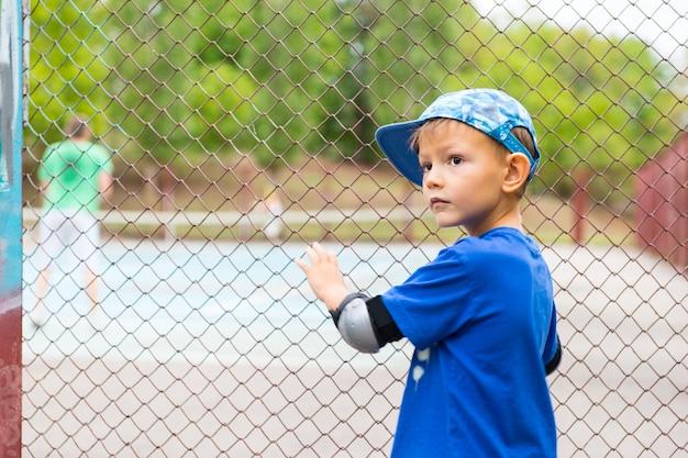 Petit garçon regardant une partie de tennis debout à la clôture en treillis métallique périphérique se retournant pour regarder par-dessus son épaule avec une expression interrogative