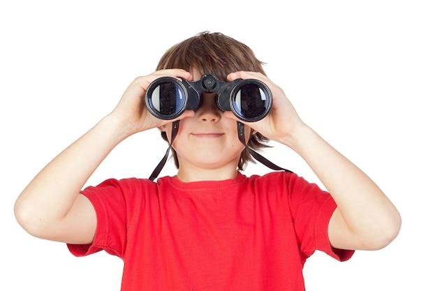 Petit garçon regardant à travers des jumelles isolé sur fond blanc