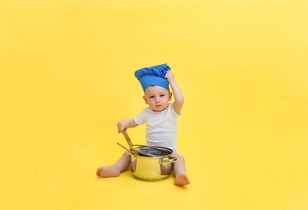 Un petit garçon regarde et une toque avec un pot et une cuillère à spatule en bois. un garçon dans un body blanc tire sur une casquette