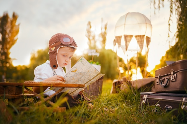 Un petit garçon rêve de devenir pilote en regardant la carte en plein air