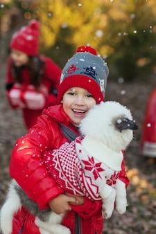 Petit garçon rit sous la neige et détient un chiot husky en pull de noël