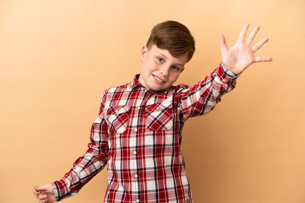 Petit garçon roux isolé sur fond beige saluant avec la main avec une expression heureuse