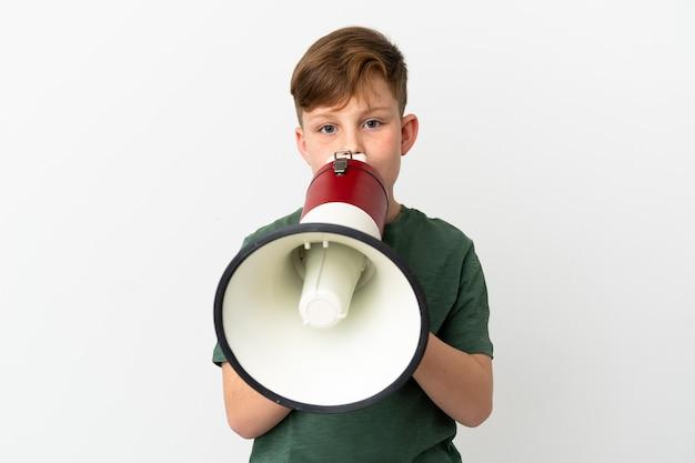 Petit garçon roux isolé sur fond blanc criant à travers un mégaphone pour annoncer quelque chose