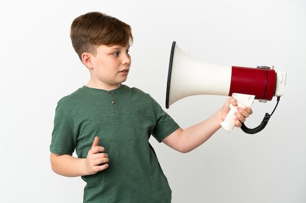 Petit garçon roux isolé sur fond blanc tenant un mégaphone avec une expression stressée