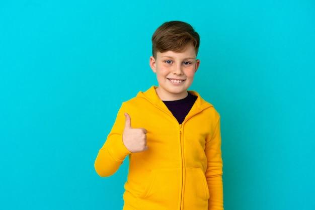 Petit garçon roux isolé sur fond bleu donnant un coup de pouce geste