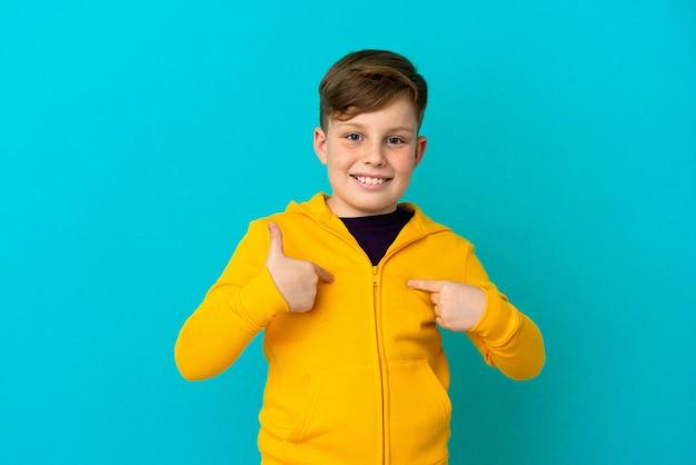 Petit garçon roux isolé sur fond bleu avec une expression faciale surprise