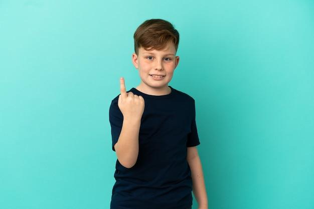 Petit garçon roux isolé sur fond bleu faisant un geste à venir
