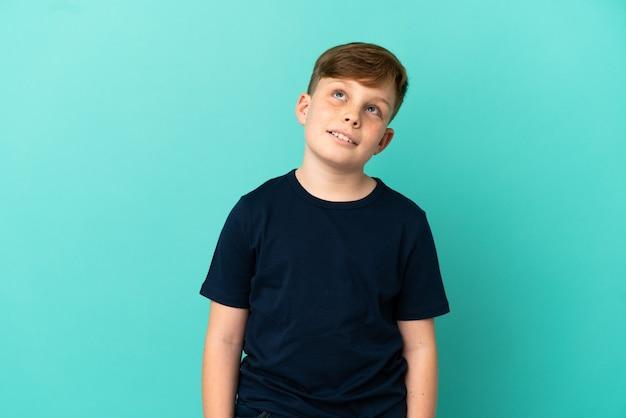 Petit garçon roux isolé sur fond bleu pensant à une idée tout en levant les yeux