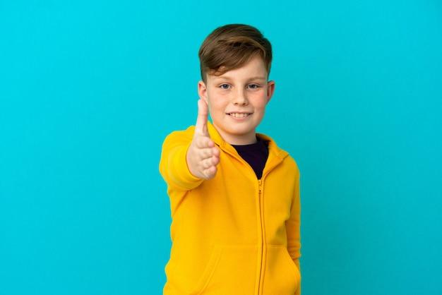 Petit garçon roux isolé sur fond bleu se serrant la main pour conclure une bonne affaire