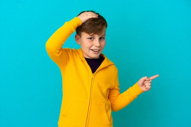 Petit garçon roux isolé sur fond bleu surpris et pointant le doigt sur le côté