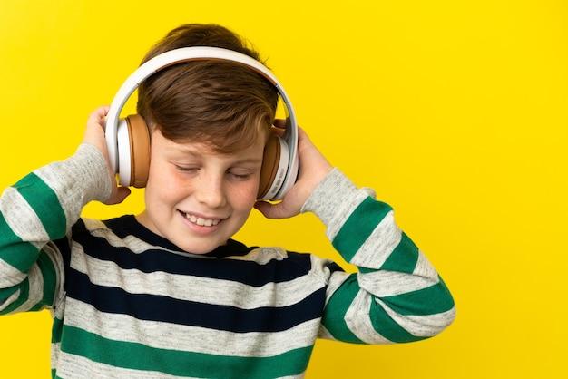 Petit garçon roux isolé sur fond jaune, écouter de la musique
