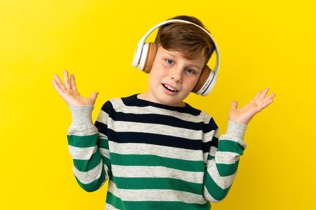 Petit garçon roux isolé sur fond jaune surpris et écoutant de la musique