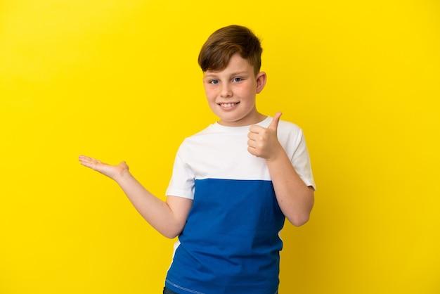 Petit garçon roux isolé sur fond jaune tenant un espace de copie imaginaire sur la paume pour insérer une annonce et avec le pouce levé