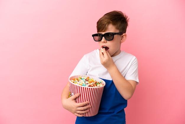 Petit garçon roux isolé sur fond rose avec des lunettes 3d et tenant un grand seau de pop-corn tout en regardant de côté