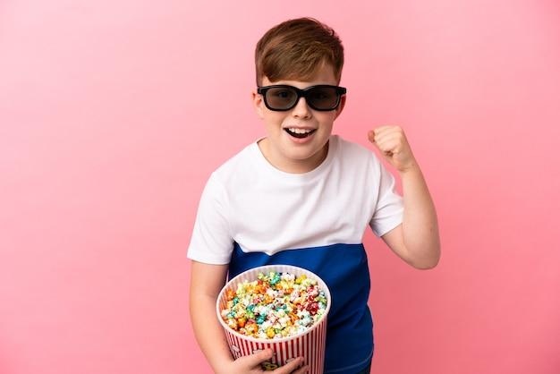 Petit garçon roux isolé sur fond rose avec des lunettes 3d et tenant un grand seau de pop-corn