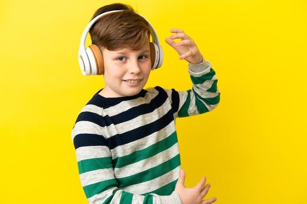 Petit garçon roux isolé sur un mur jaune écoutant de la musique et faisant un geste de guitare