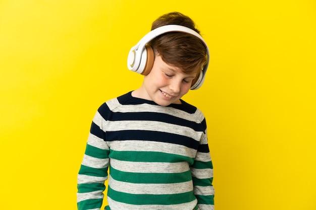 Petit garçon roux isolé sur un mur jaune en écoutant de la musique