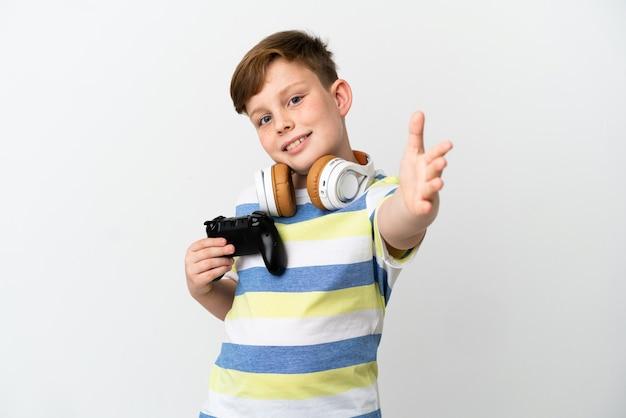 Petit garçon roux tenant une manette de jeu isolée sur fond blanc se serrant la main pour conclure une bonne affaire
