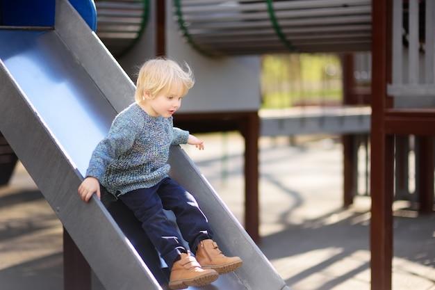 Petit garçon s'amusant sur l'aire de jeux extérieure / sur toboggan