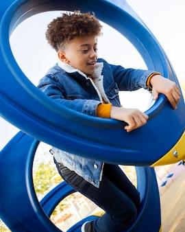 Petit garçon s'amusant sur l'aire de jeux en plein air