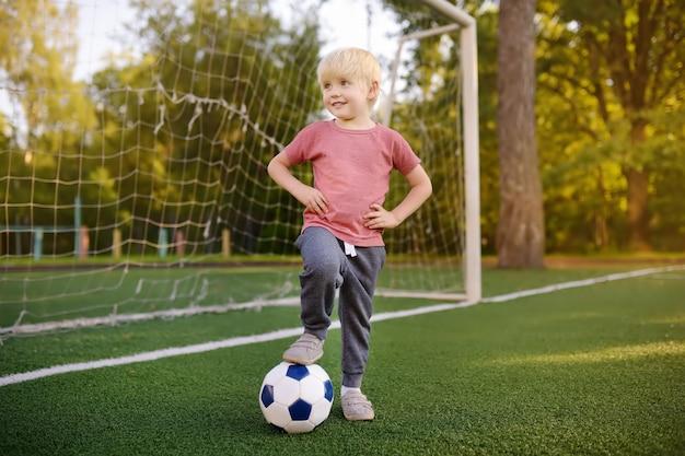 Petit garçon s'amusant à jouer à un match de foot / football le jour de l'été. jeu de plein air actif / sport pour enfants.