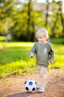 Petit garçon s'amusant à jouer à un match de foot / football le jour d'été