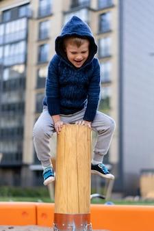 Un petit garçon s'amuse sur le terrain de jeu européen urbain moderne