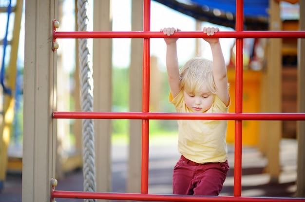 Petit garçon s'amuser sur une aire de jeux extérieure. sports d'été actifs pour les enfants
