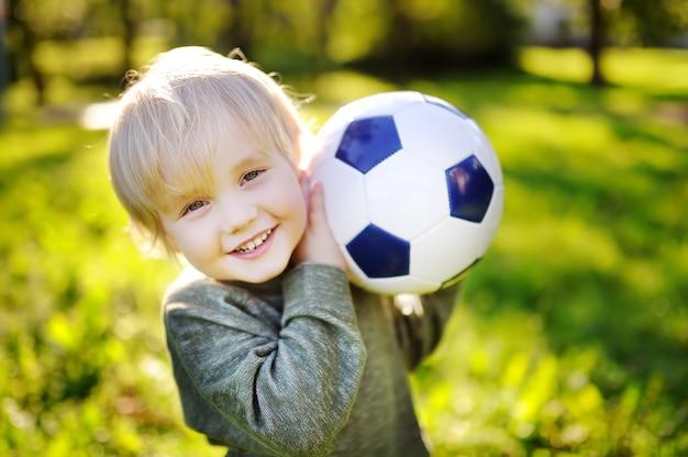 Petit garçon s'amuser jouer à un match de football sur une journée d'été ensoleillée