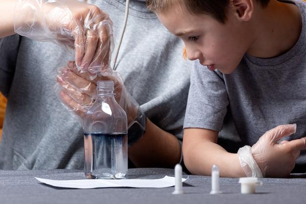Un petit garçon et sa maman ajoutent un élément chimique d'un tube à essai à une bouteille d'eau et le peignent en bleu